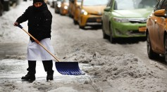 A man shovels a snow covered Manhattan street on an unseasonably cold day on March 15, 2017 in New York City.