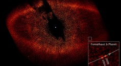 A visible-light image from the Hubble Space Telescope shows a red ring of dust and debris that surrounds the star Fomalhaut and the newly discovered planet, Fomalhaut b, orbiting its parent star.