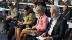 Delegates take notes during a plenary session of the U.N. Climate Change Conference COP 20 in Lima December 13, 2014.