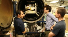 Associate Professor Joshua Rovey, left, talks about electric propulsion system testing with AE graduate students Nick Rasmont and Matt Klosterman