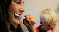 Mother and son brushing their teeth