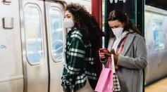 girlfriends-in-masks-using-cellphone-in-underground-station-near-train-6567595