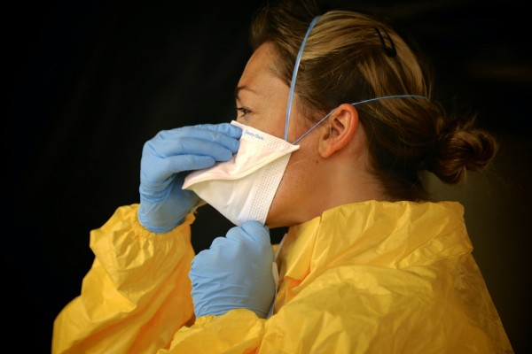 woman-in-yellow-protective-suit-wearing-white-face-mask-3992948