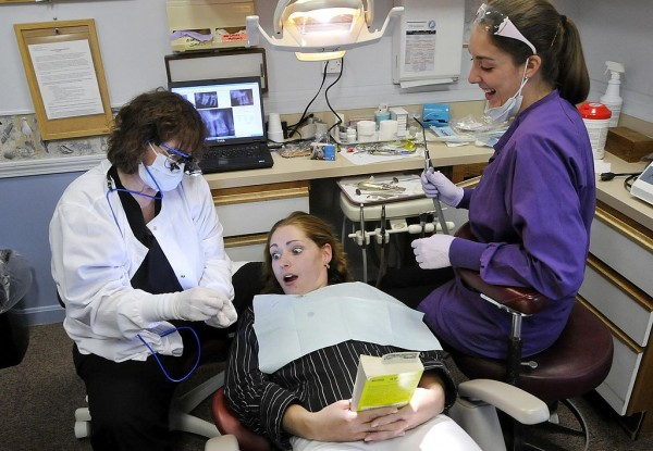 Patient Adriane Williams of Portland reacts as she is shown a wisdom tooth with a cavity