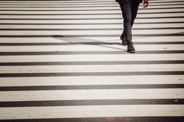 faceless-pedestrian-walking-on-crosswalk-on-sunny-day-4560160