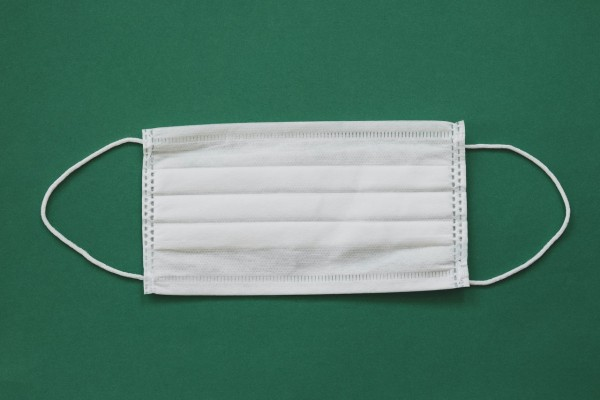photo-of-white-face-mask-against-green-background-4481591/