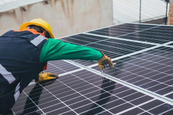 solar-technician-installing-solar-panel-8853502/