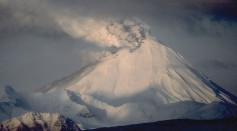 View, looking west, of 1,312-m (4,304 ft)-high Kanaga Volcano in eruption. Kanaga is located about 25 km (16 mi) west of the U.S. Navy installation and port on Adak Island in the Aleutian Islands.